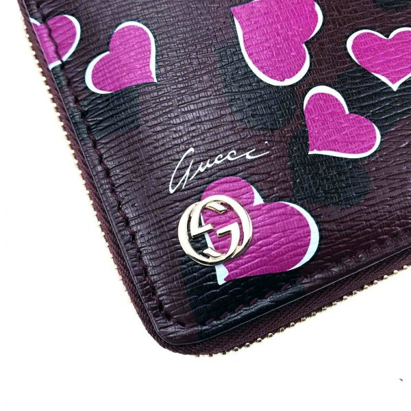 Authentic, New, and Unused Women's Gucci Magenta Heartbeat Print Leather Zippy Long Wallet 309705 golden GG plaque close-up
